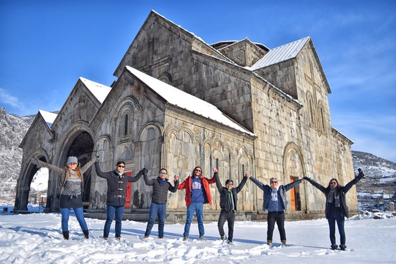 Happy Guide and toursists at Akhtala Fortress, in fron to of Astvatsatsin Church