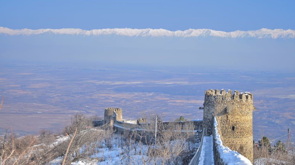 Signagi city wall covered with snow in winter caucasus mountains in the backdrop